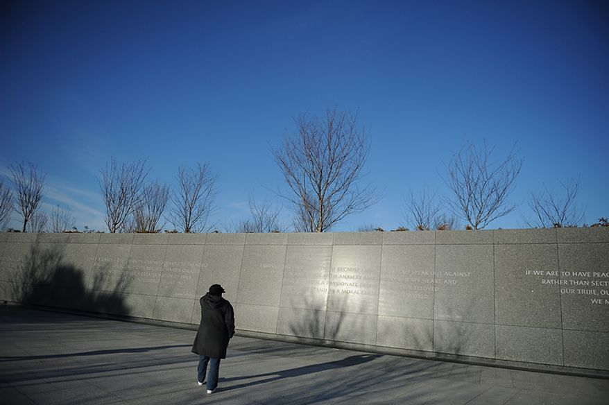 Terry Riddick of Oxon Hill reads a passage on the wall at the Martin Luther King Jr. Memorial on the National Mall in Washington on Monday, Jan. 16, 2012. (Rod Lamkey Jr./The Washington Times)