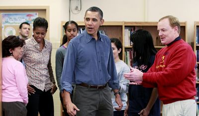 President Obama, first lady Michelle Obama and their daughter Malia are greeted Jan. 16, 2012, by Paul F. Bliss, president of the Big Brothers Big Sisters of the National Capital Area as they participate in a community service project in honor of Martin Luther King Jr., at the Browne Education Campus in Washington. (Associated Press)