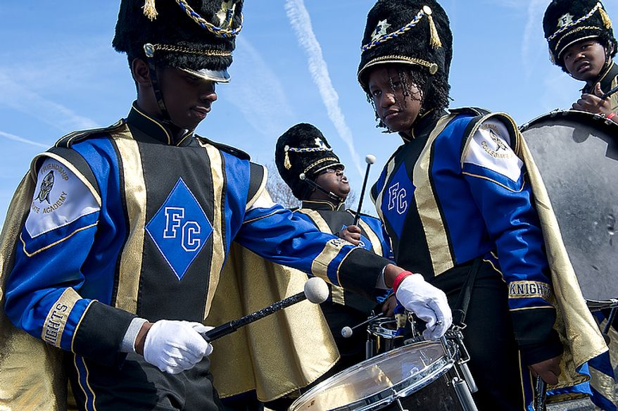 Diamante Scott, 17, left, tunes a drum while his fellow Friendship Collegiate Academy drumline members (from left) Shianell Dunn, 16, Kadesha Ransom, 17, and Ronal Greene, 14, wait for the Martin Luther King Jr. Day Parade along Martin Luther King Jr. Avenue in Southeast Washington, D.C. to begin on Monday, Jan. 16, 2012. This is the first time in eight years that the parade has been held, and more than 200 groups signed up to march. (Barbara L. Salisbury/The Washington Times)