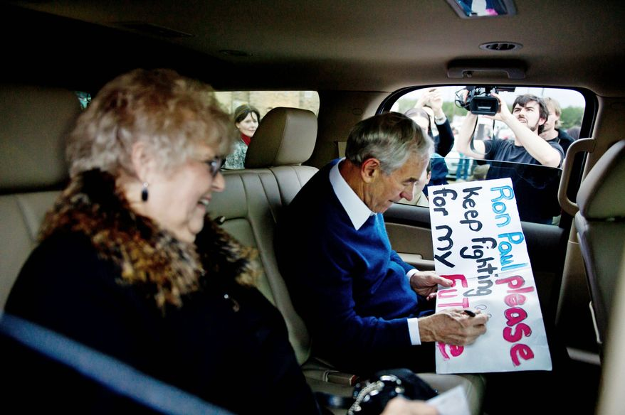 SIGNATURE POLICY: Rep. Ron Paul of Texas autographs a supporter's sign as he and his wife, Carol, leave a campaign stop in Rock Hill, S.C., on Tuesday. (Andrew Harnik/The Washington Times)