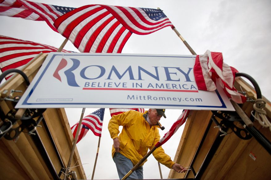 Republican Presidential candidate Mitt Romney supporter Jim Wilson of Buckingham, VA sets up flags in his truck before Romney speaks at an early morning campaign rally at the Florence Civic Center, Florence, SC, Tuesday, January 17, 2012. (Andrew Harnik / The Washington Times)