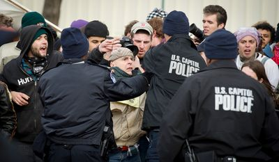 U.S. Capital Police attempt to arrest a man who came across the police line during an Occupy protest on the west lawn of the United States Capitol in Washington, D.C., Tuesday, January 17, 2012, however people in the crowds were successful pulling him back into the crowd.  (Rod Lamkey Jr/ The Washington Times)
