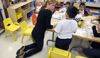Pre-kindergarten teacher Laura Amling helps her 3-year-old students with a project at Powell Elementary School in Washington on Dec. 6, 2011. The expansion in public prekindergarten programs has slowed and even been reversed in some states as school districts cope with shrinking budgets. As a result, many 3- and 4-year-olds aren't going to preschool. (Associated Press)