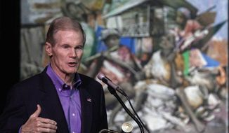Sen. Bill Nelson, Florida Democrat, speaks Friday in front of a painting by a Haitian artist at a Miami middle school about reconstruction in Haiti since a January 2010 earthquake there. Mr. Nelson is seeking a third Senate term this fall. (Associated Press)
