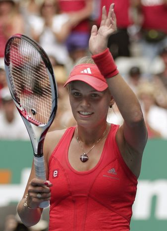 Caroline Wozniacki waves to the crowd after beating Anna Tatishvili during their second-round match at the Australian Open, in Melbourne, Australia, Wednesday, Jan. 18, 2012. (AP Photo/Rick Rycroft)