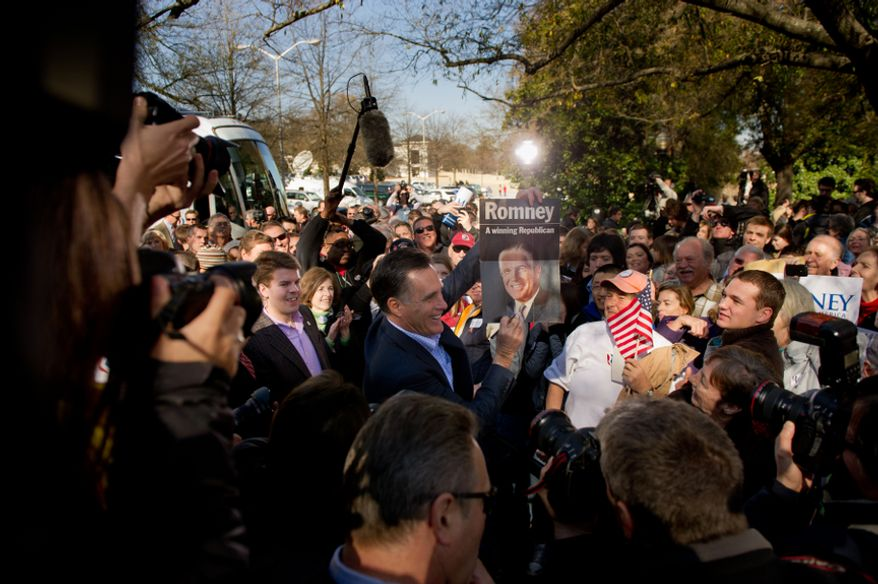 Republican presidential candidate and former Massachusetts Gov. Mitt Romney holds up an old campaign poster of his father George Romney, which a supporter handed him to sign during a campaign rally Jan. 18, 2012, on the Wofford College campus in Spartanburg, S.C. (Andrew Harnik/The Washington Times)