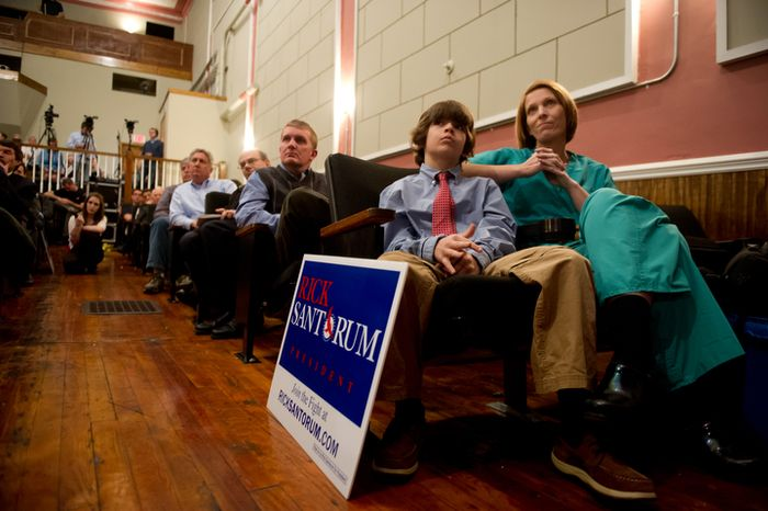 Sherry Hampton (right), a nurse from Laurens, S.C., and her 10-year-old son David listen to Republican presidential candidate and former Pennsylvania Sen. Rick Santorum speak Jan. 18, 2012, at a town hall meeting at the Capitol Theatre in Laurens. (Andrew Harnik/The Washington Times)