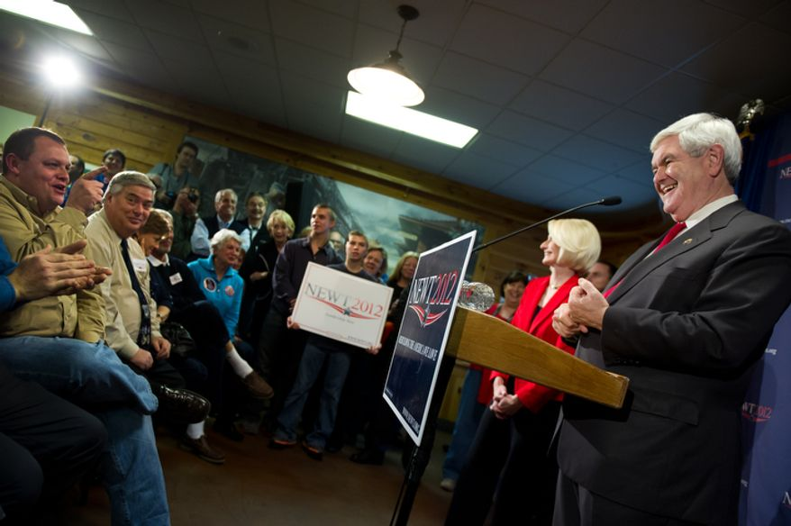 Republican presidential candidate Newt Gingrich laughs with a supporter while speaking Jan. 18, 2012, at a town hall meeting at Mutt's BBQ in Easley, S.C. At his right is his wife Callista. (Andrew Harnik/The Washington Times)