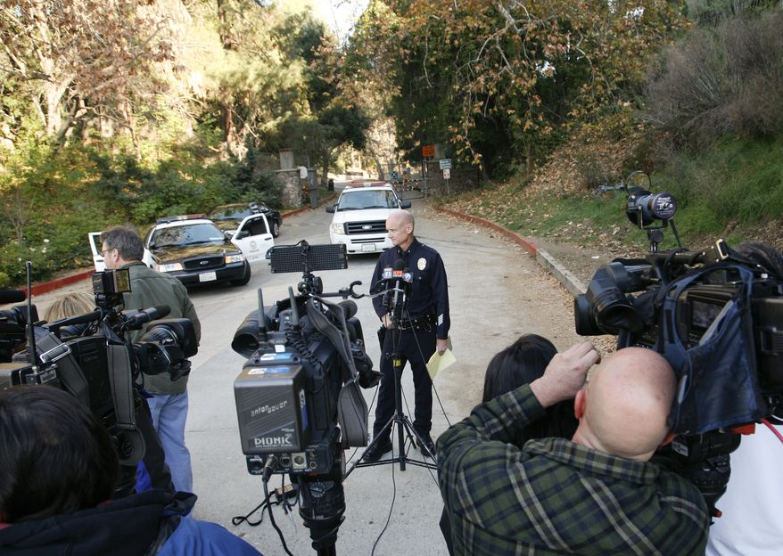 Los Angeles police Cmdr. Andrew Smith (center) prepares to speak to the media in front of the Bronson Canyon Park entrance in Los Angeles on Wednesday, Jan. 18, 2012, as detectives search the neighborhood below the Hollywood sign after a plastic bag containing a human head was discovered Tuesday on a nearby trail. (AP Photo/Jason Redmond)
