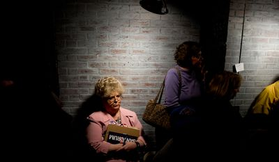 A woman in the back of the room listens as Republican presidential candidate and former Pennsylvania Sen. Rick Santorum speaks Jan. 16, 2012, at the Fresh Brewed Coffee House in Myrtle Beach, S.C., to members of CafeMom, a group of politically active South Carolina mothers. (Andrew Harnik/The Washington Times)