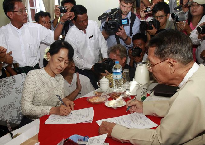 Myanmar democracy icon Aung San Suu Kyi (left) signs documents as she submits a candidate list of her National League for Democracy party for the upcoming parliamentary by-elections at the Yangon District Election Commission on Wednesday, Jan. 18, 2012, in Yangon, Myanmar. Mrs. Suu Kyi registered to run for a seat representing Kawhmu, a poor district south of Yangon. (AP Photo/Khin Maung Win)