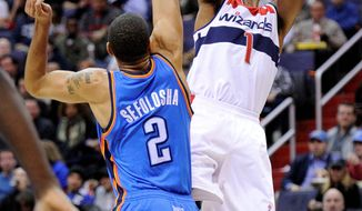 Washington Wizards guard Nick Young (1) takes a shot against Oklahoma City Thunder guard Thabo Sefolosha (2), of Switzerland, during the second half of an NBA basketball game on Wednesday, Jan. 18, 2012, in Washington. The Wizards won 105-102. (AP Photo/Nick Wass)