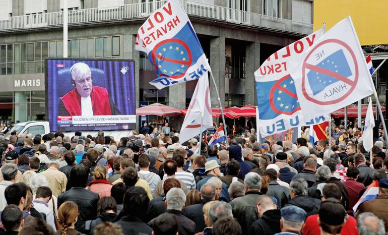 """Residents wave anti-EU flags as they watch a live broadcast from the U.N. court on the verdict for a key wartime Croatian commander, Gen. Ante Gotovina, in Zagreb, Croatia, in April. Croatia signed an EU accession treaty last year and is set to become a member in July 2013, if the Croats say """"yes"""" in the referendum and all of the bloc's 27 states later ratify the deal. (Associated Press)"""