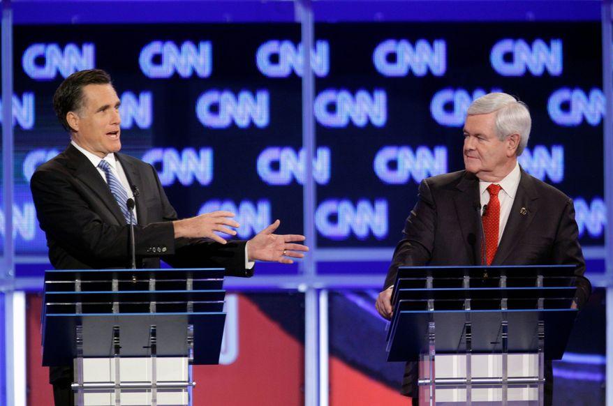 Former Massachusetts Gov. Mitt Romney (left) makes a point as former House Speaker Newt Gingrich listens during the Republican presidential candidate debate at the North Charleston Coliseum in Charleston, S.C., on Thursday. (Associated Press)