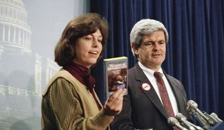 """** FILE ** Rep. Newt Gingrich looks on as his second wife, Marianne, holds up a copy of their book, """"Window of Opportunity,"""" during a news conference on Capitol Hill in Washington in March 1989. (AP Photo/John Duricka)"""