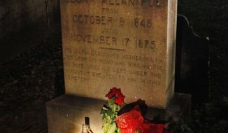 """A flashlight shines on items left on the gravestone of Edgar Allen Poe by people pretending to be the mysterious """"Poe Toaster"""" in Baltimore early on Thursday, Jan. 19, 2012. (AP Photo/Patrick Semansky)"""