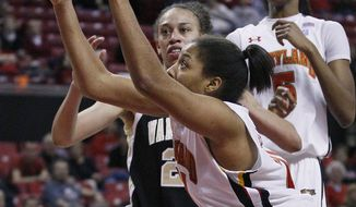 Maryland forward Tianna Hawkins, front, grabs her 24th rebound of the game in front of Wake Forest forward Dearica Hamby and teammate Essence Townsend in the second half in College Park, Md., Thursday, Jan. 19, 2012. Hawkins broke the previous team record of 23 total rebounds and also contributed a game-high 18 points to Maryland's 86-58 win. (AP Photo/Patrick Semansky)