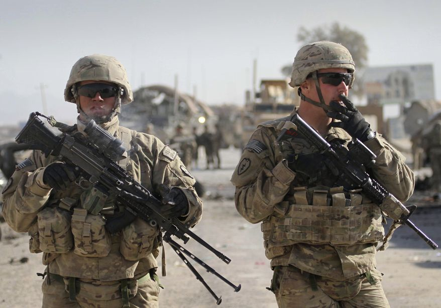 U.S. soldiers with the NATO led International Security Assistance Force (ISAF) stand guard at the scene of a suicide attack in Kandahar south of Kabul, Afghanistan, Thursday, Jan. 19, 2012. In a separate incident, a senior U.S. defense official says all six reported killed in the crash of a U.S. helicopter in Afghanistan were U.S. Marines. (AP Photo/Allauddin Khan)