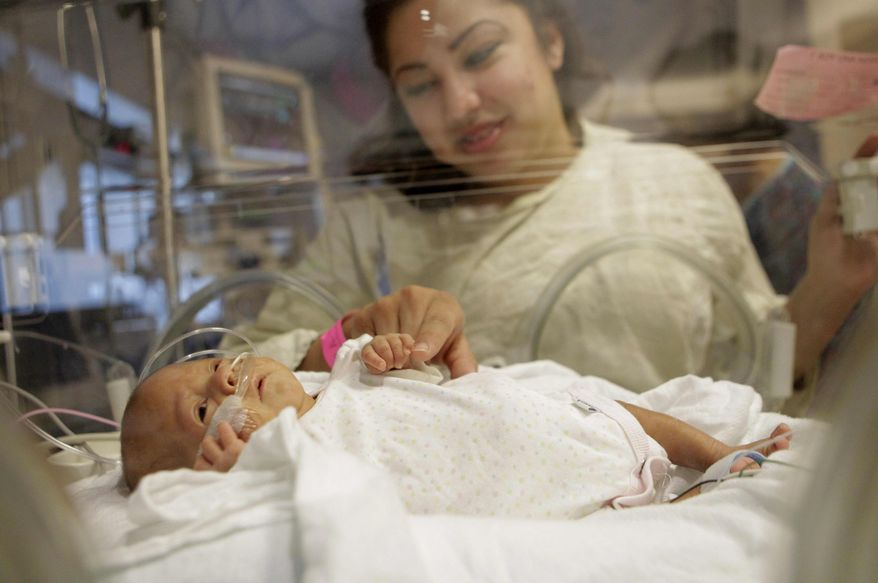 Haydee Ibarra looks at her 14-week-old daughter, Melinda Star Guido, at the Los Angeles County-USC Medical Center in Los Angeles, Wednesday, Dec. 14, 2011. At birth, Melinda Star Guido tipped the scales at only 9 1/2 ounces, less than a can of soda. After spending her early months in the neonatal intensive care unit, a team of doctors and nurses will gather Friday, Jan. 20, 2012, to see her off as she heads home. (AP Photo/Jae C. Hong)