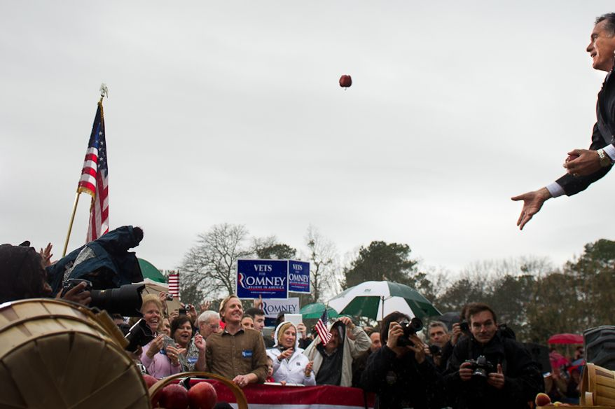 Republican presidential candidate and former Massachusetts Gov. Mitt Romney tosses an apple into the crowd before speaking Jan. 20, 2012, at a campaign rally at the Harmon Tree Farm in Gilbert, S.C. (Andrew Harnik/The Washington Times)