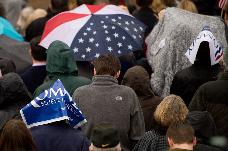Supporters of Republican presidential candidate and former Massachusetts Gov. Mitt Romney use campaign posters to shield themselves from the rain on Jan. 20, 2012, as Romney speaks at a campaign rally at the Harmon Tree Farm in Gilbert, S.C. (Andrew Harnik/The Washington Times)