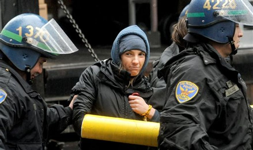 Police officers arrest an Occupy protester who was blocking Wells Fargo's corporate headquarters on Friday, Jan. 20, 2012, in San Francisco. Anti-Wall Street demonstrators across the U.S. planned rallies Friday in front of banks and courthouses. (AP Photo/Noah Berger)