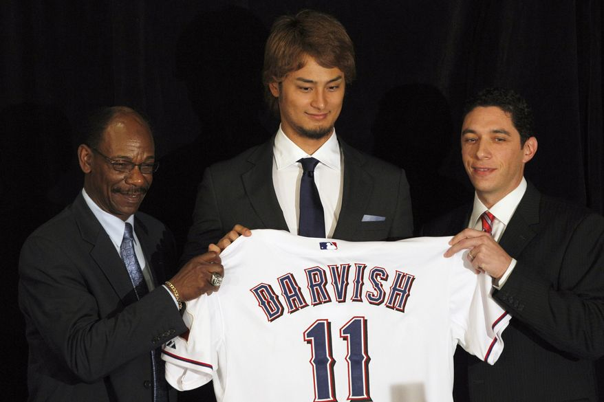 New Texas Rangers pitcher Yu Darvish poses with manger Ron Washington and general manager Jon Daniel during a news conference in Arlington, Texas, Friday, Jan. 20, 2012. (AP Photo/LM Otero)