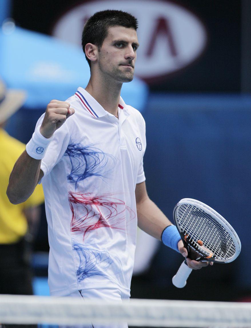 Serbia's Novak Djokovic celebrates following his win over France's Nicholas Mahut in their third-round match at the Australian Open, in Melbourne, Australia, Saturday, Jan. 21, 2012. (AP Photo/John Donegan)