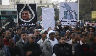 ** FILE ** Protesters hold placards depicting Egypt's ousted President Hosni Mubarak, one encircled in a noose, at a rally honoring those killed in clashes with security forces in Tahrir Square in Cairo, Egypt, Friday, Jan. 20, 2012, nearly a year after the 18-day uprising that ousted Mubarak. (AP Photo/Khalil Hamra)