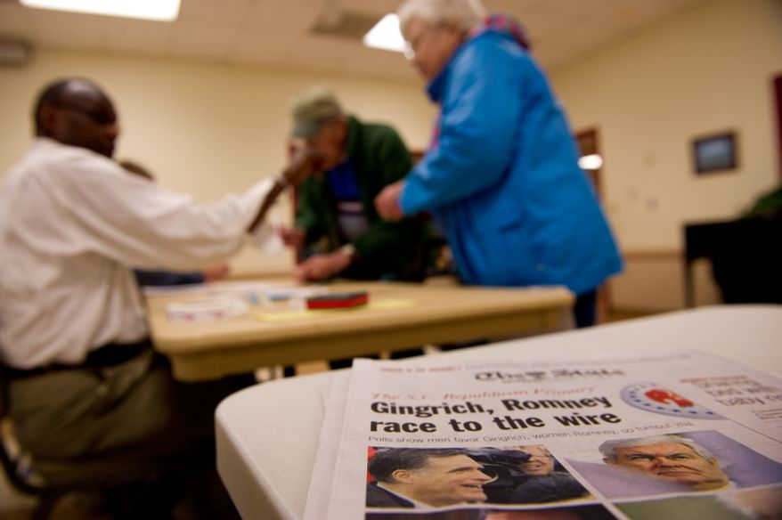 A newspaper shows Republican presidential candidates Mitt Romney and Newt Gingrich as Robert and Lois MacNaughton, center, come out to vote in the South Carolina Republican Primary at the Seven Oaks Park Community Center, Columbia, S.C., Saturday, Jan. 21, 2012. (Andrew Harnik/The Washington Times)