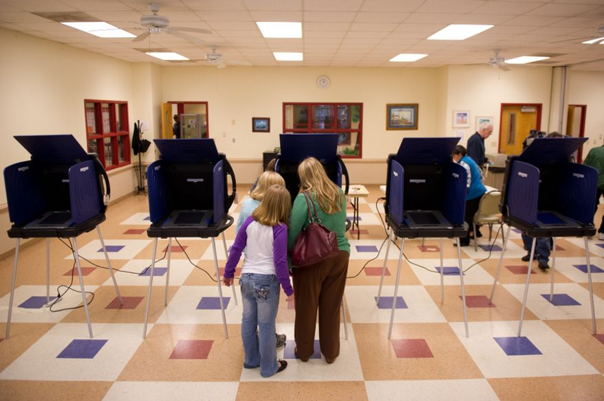 Voter Julie Weaver, center, brings her daughters, 12 year old DeAnn, and 9 year old Natalie, bottom left, as she votes in the South Carolina Republican Primary at the Seven Oaks Park Community Center, Columbia, S.C., Saturday, Jan. 21, 2012. (Andrew Harnik/The Washington Times)