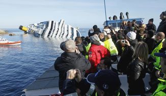 ** FILE ** People take pictures of the grounded cruise ship Costa Concordia off the Tuscan island of Giglio, Italy, Saturday, Jan. 21, 2012. (AP Photo/Pier Paolo Cito)