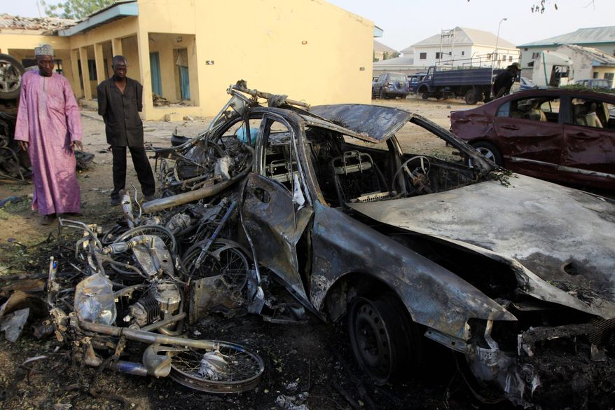 Civilians examine the police headquarters bombed by a suicide bomber in Kano, Nigeria, on Sunday. More than 150 people were killed in a series of attacks.