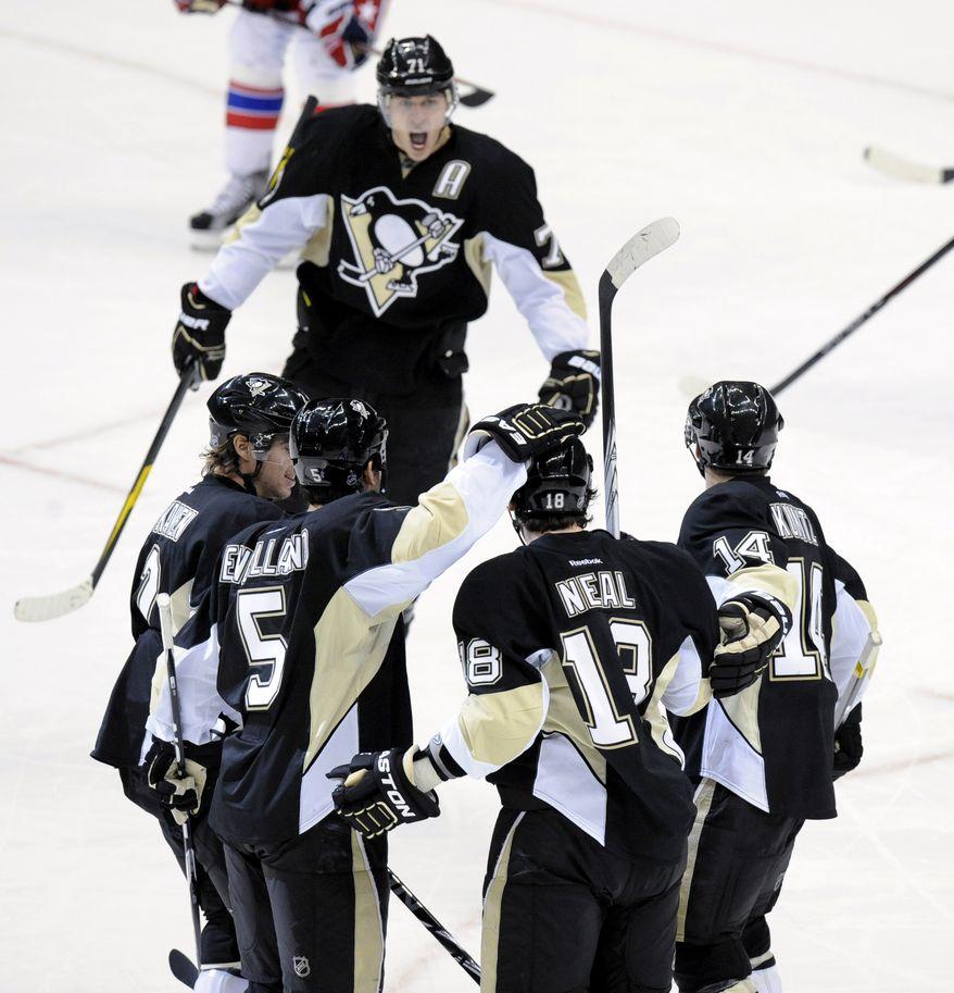 Pittsburgh Penguins' Evgeni Malkin (71), Matt Niskanen, Deryk Engelland (5), James Neal (18) and Chris Kunitz (14) celebrate following Neal's goal against the Washington Capitals during the third period, Sunday, Jan. 22, 2012, in Pittsburgh. Pittsburgh won 4-3 in overtime. (AP Photo/Don Wright)