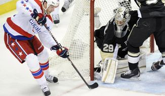 Washington Capitals center Brooks Laich (21) tries to stuff the puck past Pittsburgh Penguins goalie Marc-Andre Fleury (29) during the first period of an NHL hockey game on Sunday, Jan. 22, 2012, in Pittsburgh. (AP Photo/Don Wright)