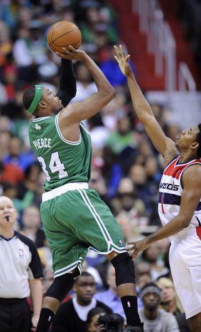 Boston Celtics forward Paul Pierce (34) takes a shot against Washington Wizards guard Nick Young (1) during the second half of an NBA game on Sunday, Jan. 22, 2012, in Washington. The Celtics won 100-94. (AP Photo/Nick Wass)