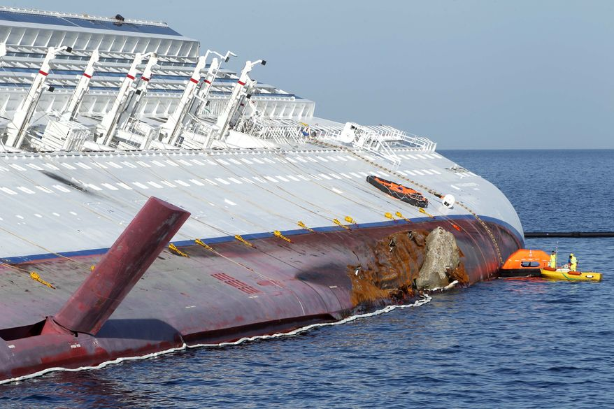 Fuel-spill experts work on the grounded cruise ship Costa Concordia off the Tuscan island of Giglio, Italy, on Saturday, Jan. 21, 2012. (AP Photo/Pier Paolo Cito)
