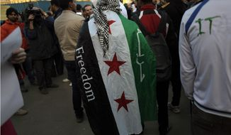 An anti-Syrian regime protesters wears a revolutionary flag on his back during a protest outside the Arab League headquarters in Cairo, Egypt Sunday, Jan. 22, 2012. Arab League foreign ministers, meeting in Cairo, extended the much-criticized observers mission for another month, officials from the 22-member organization said. The League decided to add more observers and provide them with additional resources, the officials said. (AP Photo/Nasser Nasser)