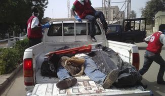Red Cross officials collect bodies from a street in Kano, Nigeria, on Saturday, Jan. 21, 2012, after a bomb blast and gun attacks Friday night. (AP Photo/Salisu Rabiu)