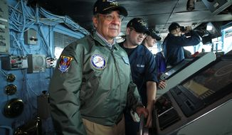 Defense Secretary Leon E. Panetta (foreground) pilots the aircraft carrier USS Enterprise as Seaman Chris McCarter assists during Mr. Panetta's visit to the ship on Saturday, Jan. 21, 2012, off the southeastern coast of the United States. (AP Photo/Alex Wong, Pool)