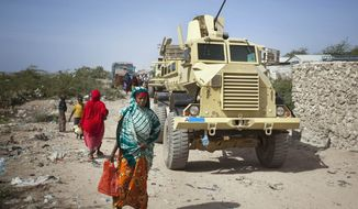 A displaced Somali woman walks past an armored vehicle of an African Union peacekeeping force that was transporting journalists in Mogadishu, Somalia, on Thursday, Jan. 19, 2012. (AP Photo/Ben Curtis)