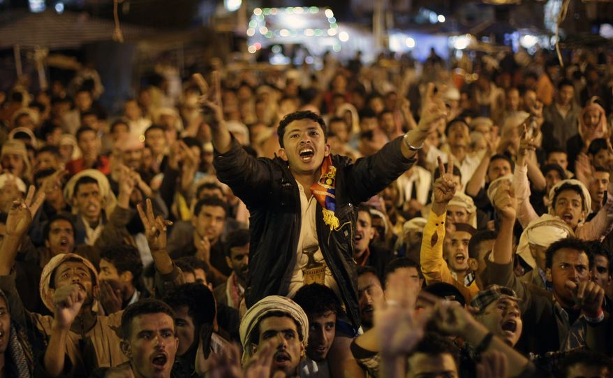 Protesters in Sanaa, Yemen, react after receiving the news of the departure of Yemeni President Ali Abdullah Saleh for Oman on Sunday, Jan. 22, 2012. (AP Photo/Hani Mohammed)