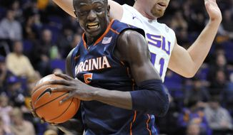 ** FILE ** In this Jan. 2, 2012, photo, Virginia center Assane Sene (5) pulls down a rebound in front of LSU center Justin Hamilton during an NCAA basketball game in Baton Rouge, La. Virginia missed its injured defensive specialist during Sunday's loss to Virginia Tech. (AP Photo/Bill Feig)