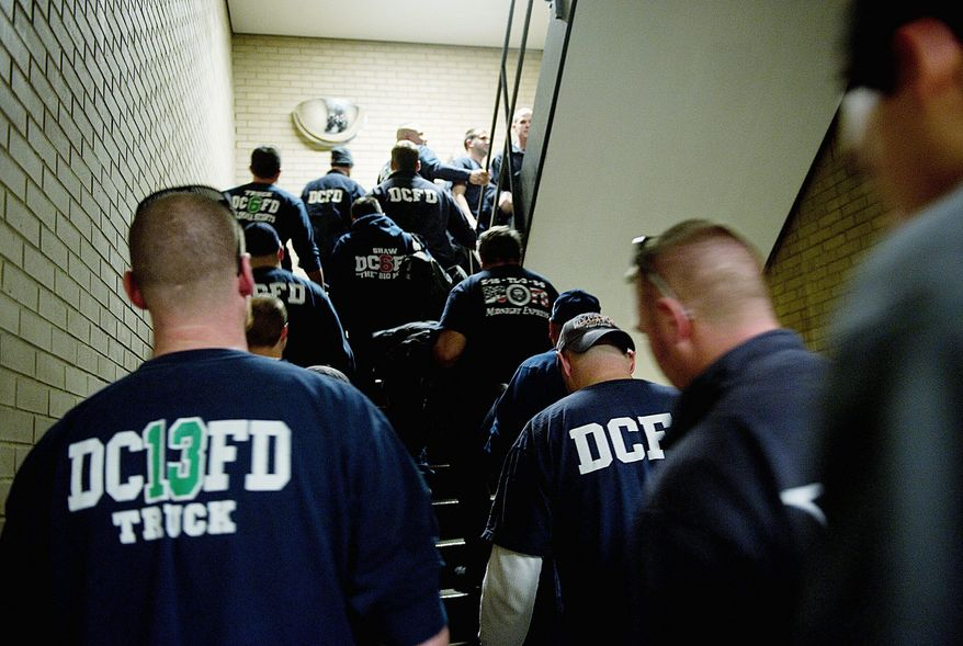 D.C. firefighters walk out of the Martin Luther King Jr. Memorial Library in Northwest on Tuesday after a speech by fire Chief Kenneth Ellerbe (Barbara Salisbury/THE WASHINGTON TIMES)
