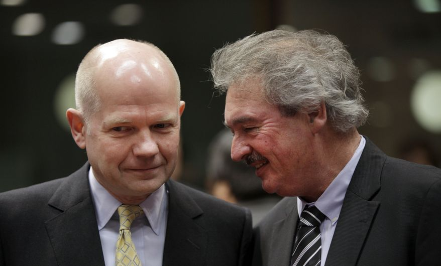 British Foreign Minister William Hague (left) speaks Jan. 23, 2012, with Luxembourg's Foreign Minister Jean Asselborn during a meeting of EU foreign ministers at the EU Council building in Brussels. (Associated Press)