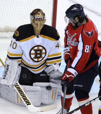 Boston Bruins goalie Tuukka Rask (40) stops a shot as Washington Capitals' Matthieu Perreault watches during the first period of an NHL game, Tuesday, Jan. 24, 2012, in Washington. (AP Photo/Richard Lipski)