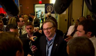 ** FILE ** Eric Fehrnstrom (center), senior campaign adviser for Republican presidential candidate Mitt Romney, talks with reporters in the spin room following the GOP candidates' debate at the University of South Florida in Tampa, Fla., on Monday, Jan. 23, 2012. (Rod Lamkey Jr./The Washington Times)