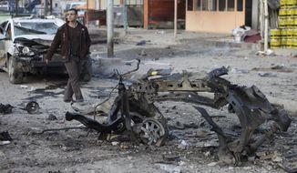 A man inspects the scene of a car bombing in the Sadr City neighborhood of eastern Baghdad on Tuesday, Jan. 24, 2012. (AP Photo/Karim Kadim)