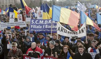 **FILE** Anti-government protesters wave banners during a demonstration march in Bucharest, Romania, on Jan. 24, 2012. The protesters called for the resignation of the country's president and early elections. (Associated Press)