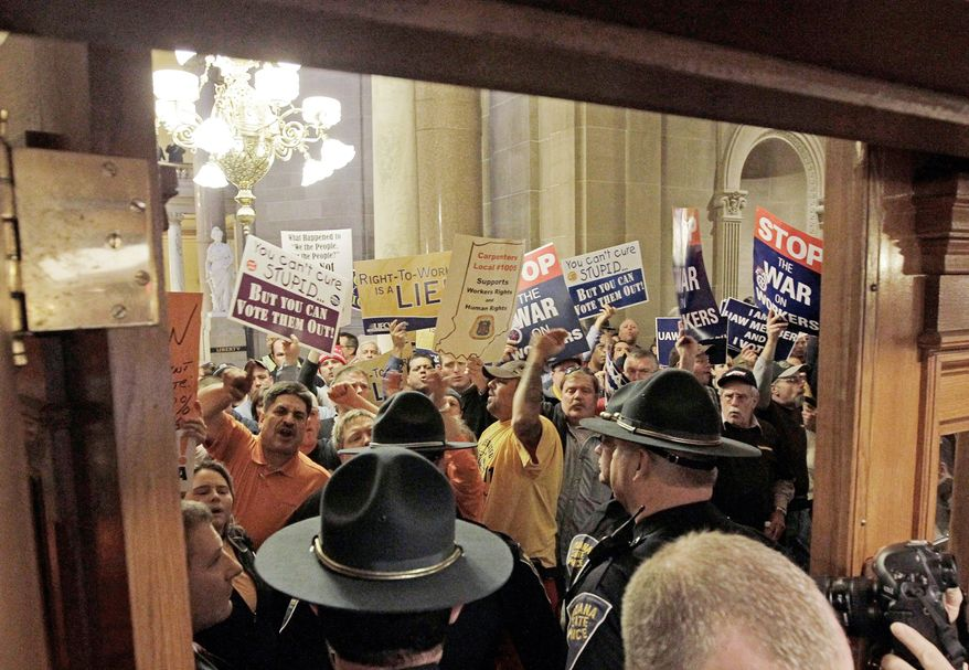 Indiana State Police stand guard at the entrance of the House of Representatives in Indianapolis during a debate Wednesday on a bill that would make Indiana the nation's 23rd state with a right-to-work law. Democrats fought the measure, which would ban unions from collecting mandatory dues from workers. (Associated Press)